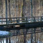 Träbro speglas i vatten